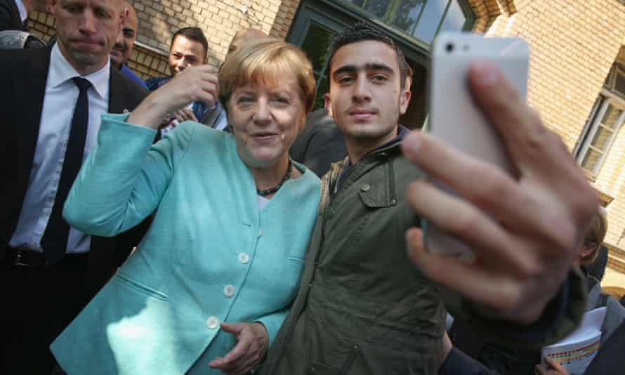 Anas Modamani takes a selfie with Angela Merkel in Berlin in September 2015