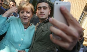 Angela Merkel poses with a migrant from Syria at a shelter in Berlin.
