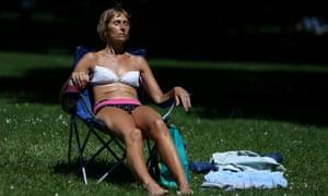 A woman in a bikini sitting on a foldaway chair in Green Park, London