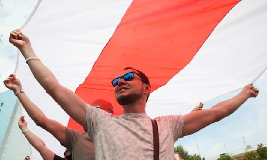 Opposition activists stretch out a flag during a rally in Minsk, Belarus.