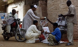 Sudanese men gather around a newspaper street vendor outside Khartoum, 2015.