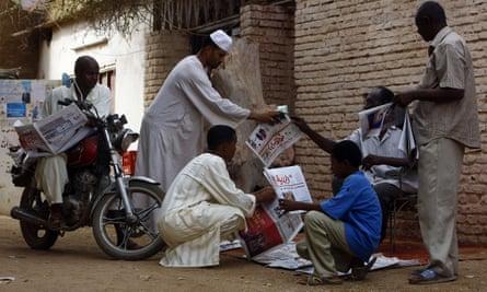 Sudanese men gather around a newspaper street vendor outside Khartoum, 2015.