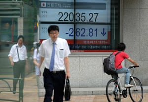 Pedestrians walking past a stock indicator showing share prices of the Tokyo Stock Exchange in Tokyo.