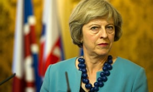 Theresa May listens to questions at a press conference.
