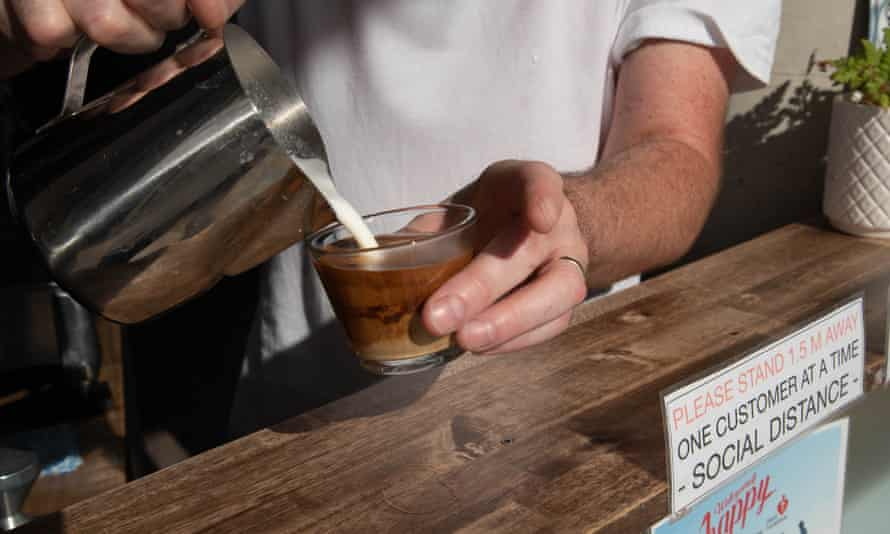 A barista pours a coffee.