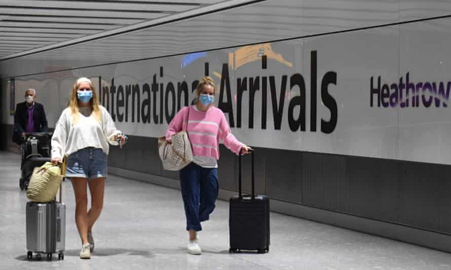 Passengers wearing face masks arrive at Heathrow airport.