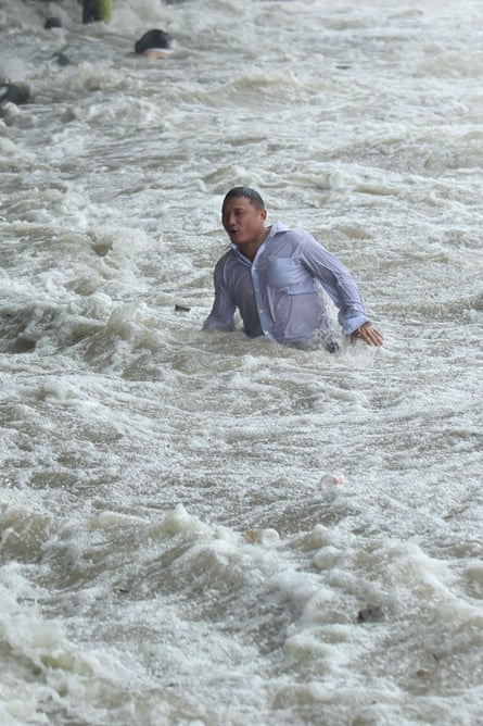 A man by the Qiantang river after Typhoon Dujuan hit China. Claims for flood damage could affect financial stability.
