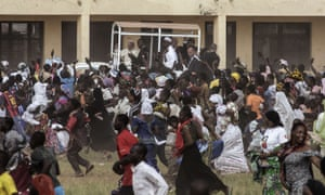 Crowds run after Francis during a visit to the Koudoukou school after leaving the mosque in Bangui.