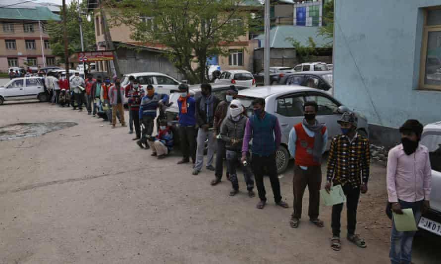 Migrant workers queue for medical examinations outside a hospital in Srinagar.