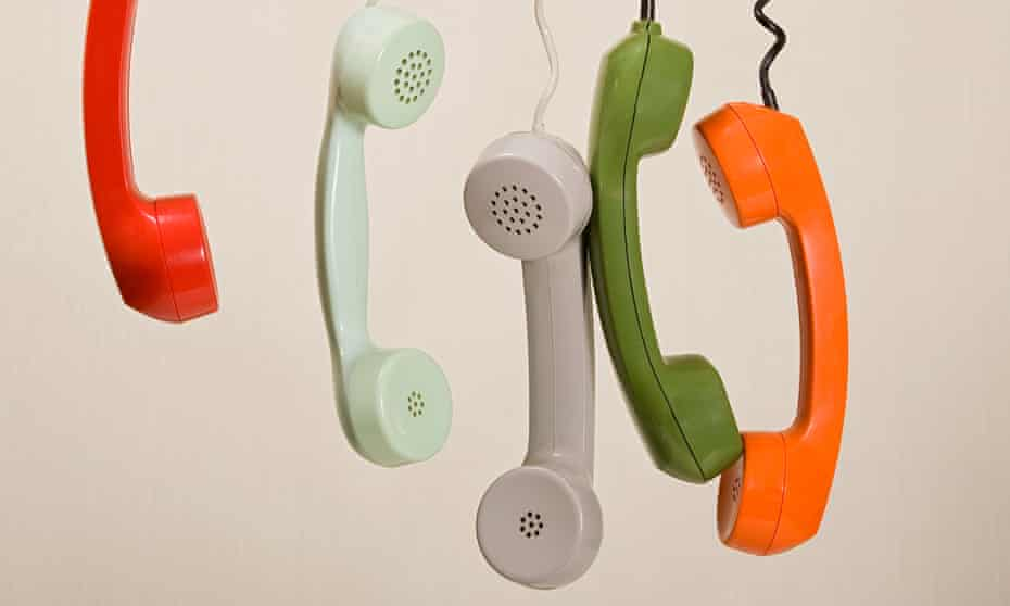 Five colourful handsets hanging in a row