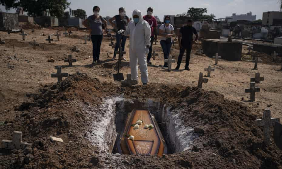 A cemetery worker stands before the coffin of a woman who is suspected to have died of Covid-19, at her burial in Rio de Janeiro.