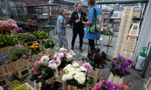A flower stall holder chats to customers.
