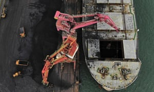 Machines load imported coal from a cargo vessel in Rizhao, China