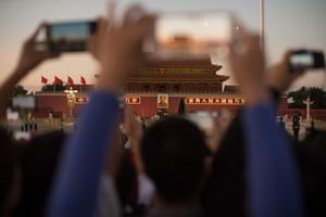 People photograph and film the lowering of the Chinese flag on Tiananmen square with their smartphones before the congress