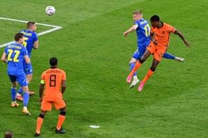 Denzel Dumfries of Netherlands scores their side's third goal whilst under pressure from Oleksandr Zinchenko of Ukraine.