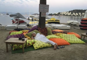 A man sleeps on the beachfront after spending the night outdoors in Bitez, near Bodrum