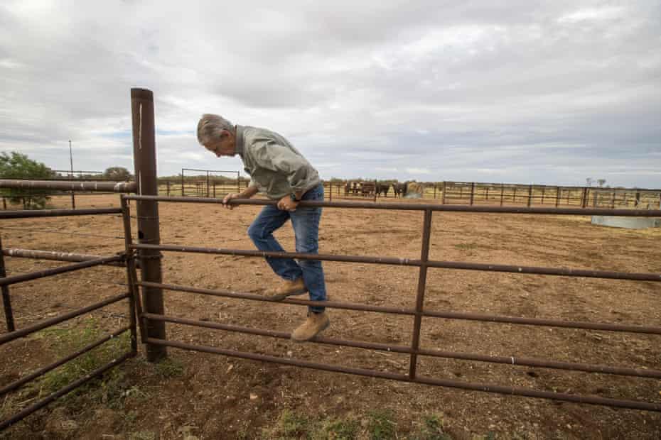 John Knight climbs a gate