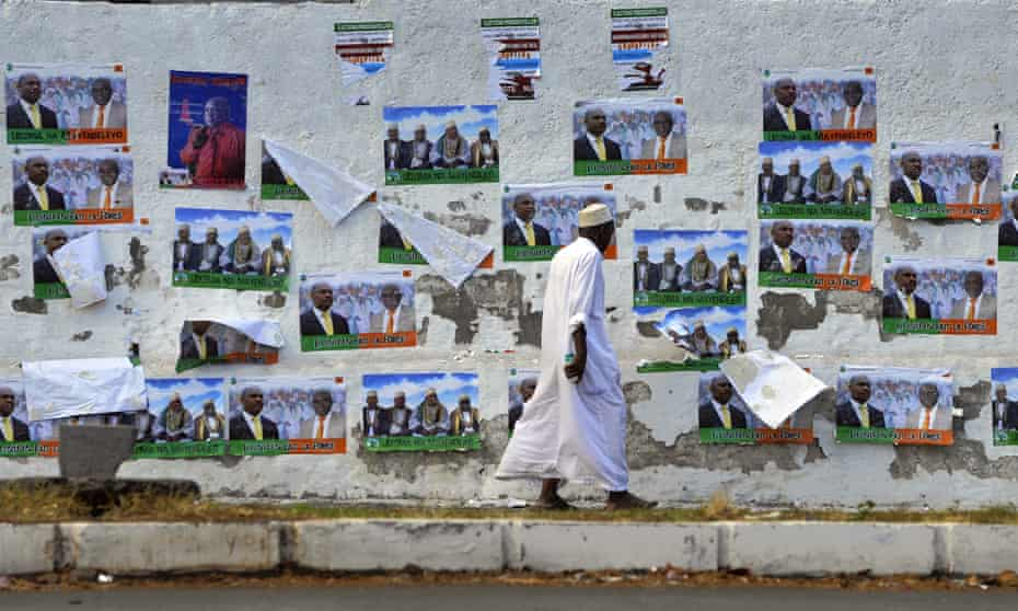 A Comoran walks past campaign posters on his way to vote during the presidential elections on December 26, 2010 in the capital Moroni.