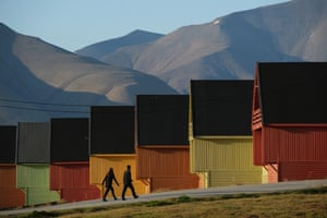 Longyearbyen, Norway. People walk past houses, with mountains devoid of snow in the background, during a summer heatwave on Svalbard archipelago