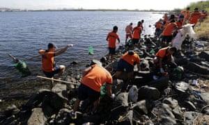 Las Piñas City, Philippines - Coastguards collect floating plastic rubbish on the coast of Freedom Island