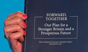 Theresa May holds up the Conservative manifesto at its launch.