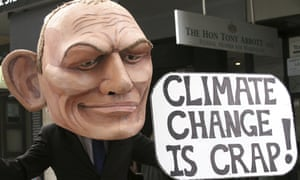 """a protester dressed as Tony Abbott with a """"climate change is crap"""" sign"""
