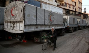 A Syrian man pushes his bicycle past a Red Crescent convoy carrying humanitarian aid in Kafr Batna on the outskirts of the capital Damascus.