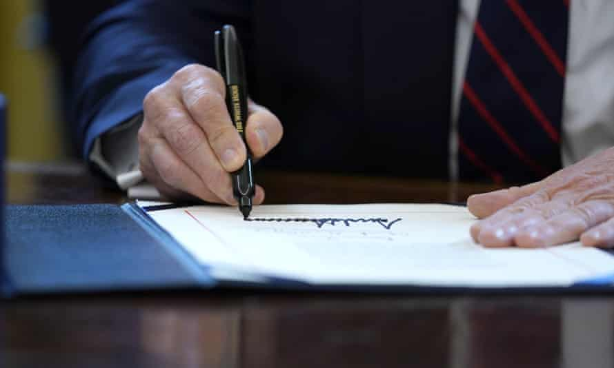 Donald Trump signs the coronavirus stimulus relief package in the Oval Office. He has insisted on his name appearing on all stimulus checks being sent out to taxpayers.