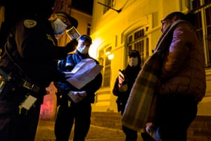 French police check a mobility form required by citizens to go outside of their homes, in an effort to stem the spread of COVID-19, during curfew on the streets of Mulhouse.