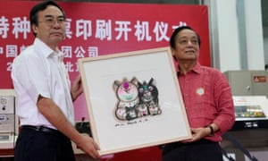 Designer Han Meilin presents his design manuscript for a Year of the Pig stamp to Liu Aili, president of China Post.