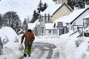 A man walks through snow in Leadhills, Scotland