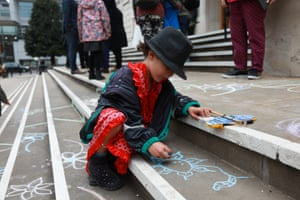 A child draws on the steps with chalk.