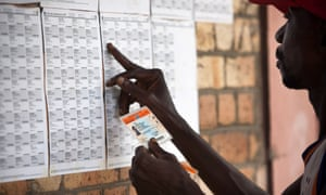 A man looks for his name on a list at a polling station in Kinshasa in 2011