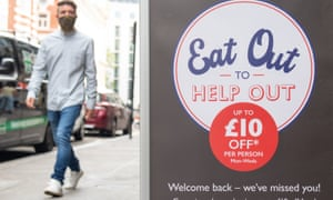 A man passing a sign advertising the 'eat out to help out' scheme.