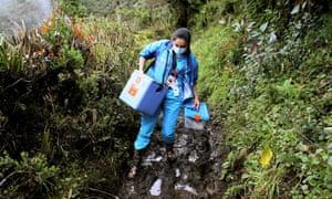 Sumapaz, Colombia: Health worker Elizabeth Romero walks carrying doses of Sinovac Covid-19 vaccine in Sumapaz, Bogota's rural zone
