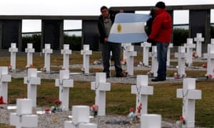 Falklands war veterans display an Argentine flag as they pay homage to Argentine soldiers who died during the conflict at Darwin cemetery in the Falkland Islands.