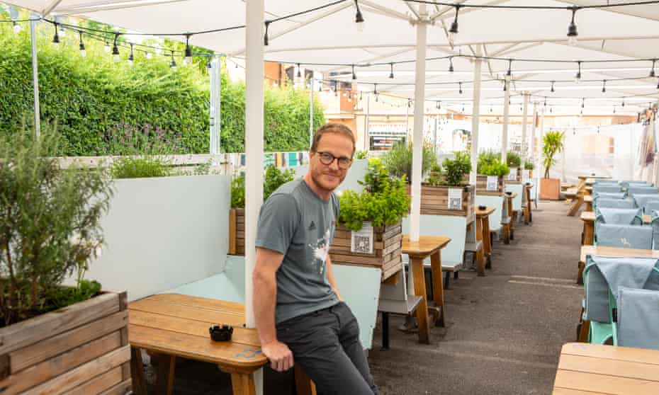 Ed Whinney, in a T-shirt and jeans, leaning against one of a number of outdoor tables under canopies at his pub