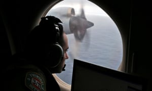 A flight officer looks out of an RAAF AP-3C Orion as it flies over the southern Indian Ocean during the search for missing flight MH370.