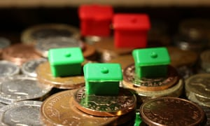 Monopoly houses and hotels sit atop penny coins