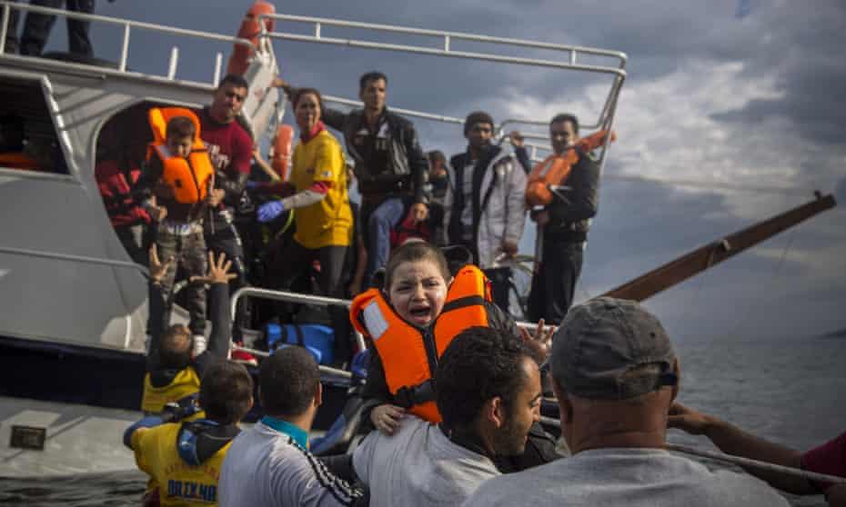 Volunteers help refugees arriving on the Greek island of Lesbos, November 2015