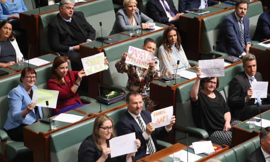 Federal Labor MPs hold up signs supporting AAP in the House of Representatives in Canberra on Tuesday after the wire service's June closure was announced