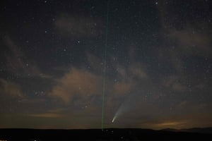 Neowise appears next to a green laser beam on 15 July used by the Haute-Provence Observatory to indicate celestial objects, in south-east France