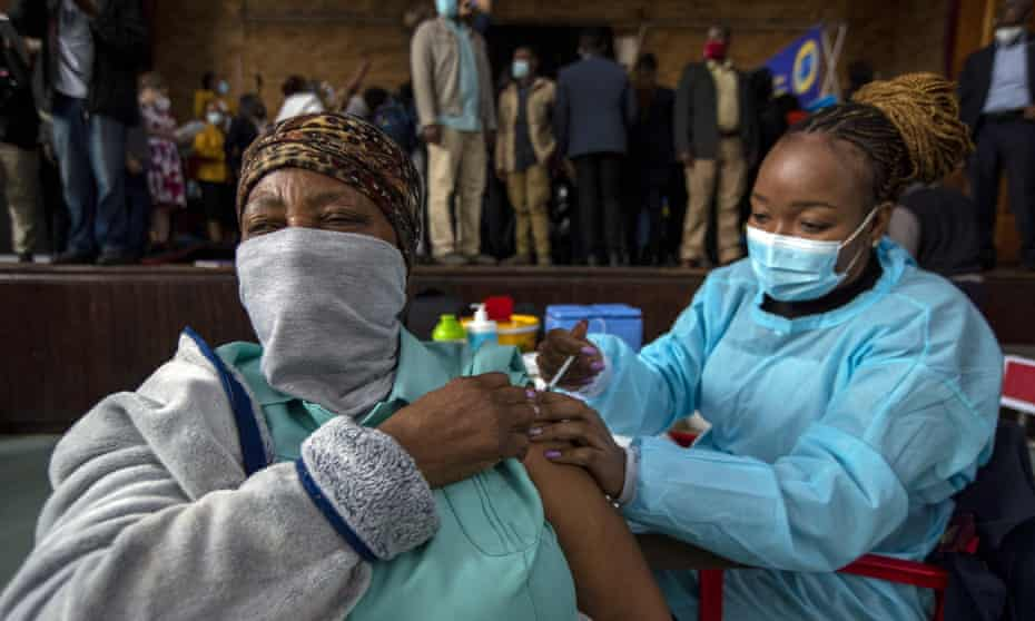 A healthcare worker gives a Covid jab to a woman in Katlehong, South Africa