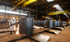 An employee cutting a sample from a roll of coiled steel inside Liberty House Group's rolling steel mill in Newport.