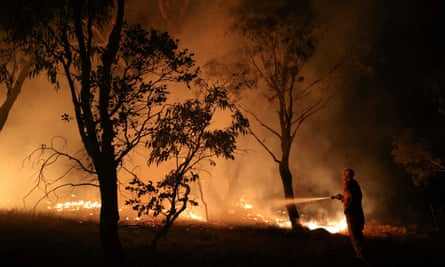 A firefighter works to extinguish flames after a bushfire burnt through the area in Bredbo, New South Wales, Australia, February 2, 2020.