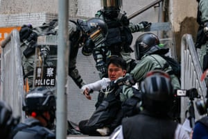 A protester is surrounded by police