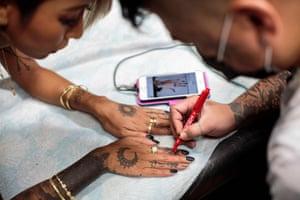 A customer gets an initial pen design on her fingers at a tattoo studio in Tsurugashima, Saitama prefecture