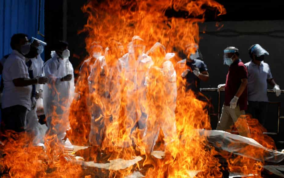 Relatives wearing personal protective equipment (PPE) attend the funeral of a man who died from Covid, at a crematorium in New Delhi on 21 April