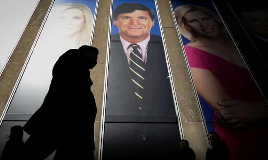 People pass by a promo of Fox News host Tucker Carlson on the News Corporation building in New York, in 2019.