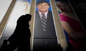 People pass by a promo of Fox News host Tucker Carlson on the News Corporation building in New York, New York, on 13 March.